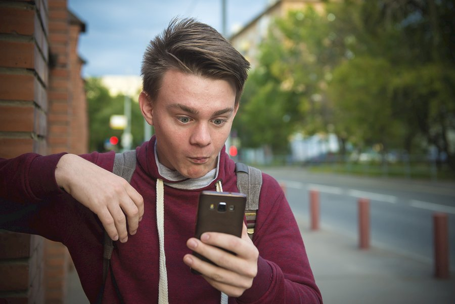 slideshow can be bad news. Teen boy reads sms on smartphone
